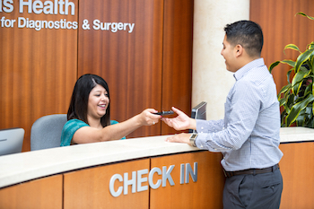 A Texas Health Center for Diagnostics and Surgery Staff Member Greets a Patient at the Check-in Desk